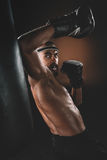 Aggressive young Muay Thai fighter in boxing gloves training thai boxing. Action sport concept Stock Photography
