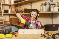 Beautiful caucasian young woman working in carpentry workshop at table place