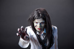 Aggressive zombie girl stretching her hand Royalty Free Stock Photos