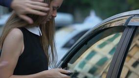Aggressiver Dieb, der Mädchen zum Auto, Geld und Schmuck stehlend, Autoentführung drängt stock footage