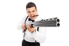 Aggressiver Mann, der mit einer Schrotflinte droht Lizenzfreie Stockfotos