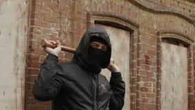 Aggressiver Rowdy in der Maske und Haube, die Baseballschläger hält stock footage