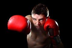 Aggressives Kämpfermann-Trainingsschattenboxen mit den roten kämpfenden Handschuhen, die schändlichen rechten Durchschlag werfen Lizenzfreie Stockfotografie