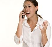 Aghast. A young woman looks aghast as she talks on the phone Stock Photography