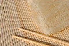 Aghi del riso su una stuoia di posto di bambù Immagine Stock