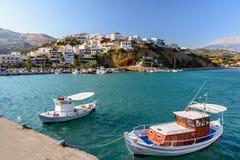 Aghia Galini镇港口有停放的渔船和美丽的房子的在克利特海岛,希腊的岩石的 免版税库存照片