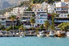 Aghia Galini镇PHarbour有停放的渔船和美丽的房子的在克利特海岛的岩石的 库存照片