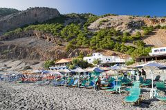 Beach with loungers and parasols at Crete island, Greece. AGIA ROUMELI, CRETE - SEPTEMBER 23: Small beach with loungers and umbrellas at Samaria gorge national Royalty Free Stock Images