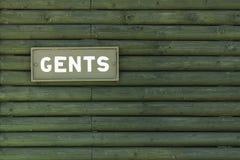 Agianst знака GENTS деревянный дом Стоковая Фотография