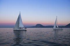 Żagiel łodzie blisko skalistych brzeg po zadziwiającego zmierzchu Podróż Obrazy Royalty Free
