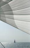 Żagiel przeciw niebieskiemu niebu, morzu i jachtom, Zdjęcia Stock