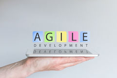 Agile development concept for mobile devices. Hand holding tablet Royalty Free Stock Photo
