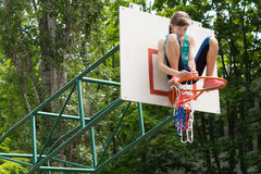 Agile young girl fixing a net on a basketball goal. Post sitting on top of the metal hoop attaching it with her hands stock photography