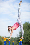 Agile young gymnast balancing on cross bars Stock Image