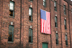 Aging barrels for bourbon whiskey. American flag hanging on a 200 year old brick wall of a distillery with bourbon barrels aging inside Royalty Free Stock Photography