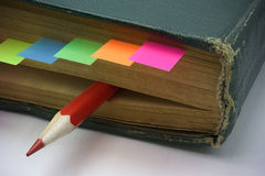 Aging book with bookmark and red pencil Royalty Free Stock Image