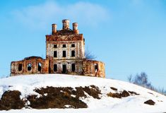 Aging church on hill. Rubble of the old temple on hill with snow on background blue sky Stock Photo
