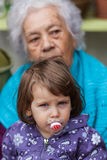 Aging concept. Young baby girl and elder women portrait royalty free stock image