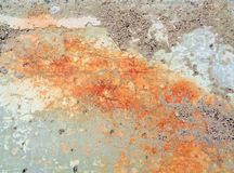 Aging Concrete Textural. This is a closeup image of an aging concrete slab. It is outdoors exposed to the elements. Rust stains in bright orange hues against royalty free stock image