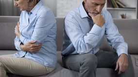 Aging couple sitting on sofa turned away from each other, family crisis, quarrel stock photography