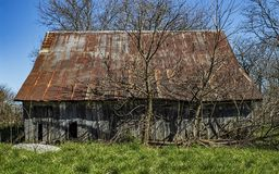 A aging distress barn in a rural area. A distressed barn with a rusting metal rood in a rural setting Royalty Free Stock Photos