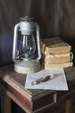 Aging kerosine lamp with book and feather to rest upon wooden ta. Ble Royalty Free Stock Photo