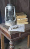 Aging kerosine lamp with book and feather to rest upon wooden ta. Ble Royalty Free Stock Image