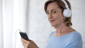 Aging lady in headphones holding mobile phone scrolling screen, choosing song. Stock photo stock photography