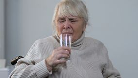 Aging lady in wheelchair taking pill and drinking water, high blood pressure stock footage