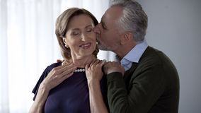 Aging male presenting pearl necklace to wife and kissing her celebration present stock images
