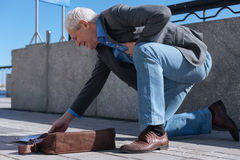 Aging man having heart attack outdoors. Suffering from unexpected pain. Senior puzzled ill man walking on the quay while expressing discomfort and having sudden stock image