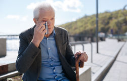 Aging man having tears of happiness on the promenade. Crying for no reason. Stylish neat exited grandfather sitting and wiping his eye with a handkerchief while stock images