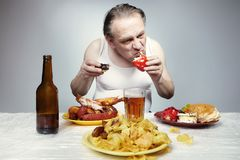Older man in a-shirt eating junk unhealthy meals. Aging man in a-shirt eating lot of junk unhealthy food royalty free stock photo