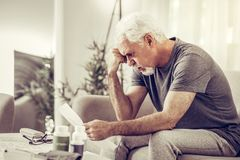 Aging mister clutching his head in despair while holding papers. Clutching head in despair. Aging upset grey-haired mister wearing grey t-shirt clutching his stock image