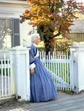 Aging mother watches from gate. Re-enactment volunteer watches at gate for her returning war hero son or husband.  White wooden fence and sidewalk Stock Photography