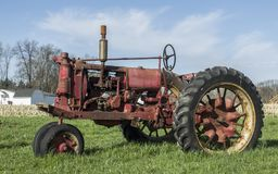 An aging red tractor in a rural area. A vintage red tractor in a field in a rural area Royalty Free Stock Photos