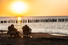 Aging sea at sunset. People sitting on sunbeds at sunset Royalty Free Stock Photography