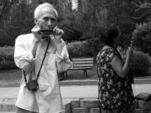 Aging society. Park, a retired old man practicing harmonica, Taiyuan, Shanxi shooting time 2001 royalty free stock images