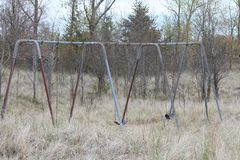 Rusty Swing Set in Park. Aging swing set in a nature area with tall grass growing around it royalty free stock image