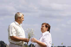 Aging together. Couple with flowers Stock Images