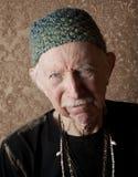 Aging Tough Guy. Senior tough guy in green knit cap leaning Royalty Free Stock Image