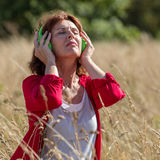 Aging woman comforting senses with music in high grass field. Outdoors music - relaxed 50s woman listening to music with headphones alone in long summer grass Stock Photos