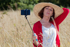 Aging woman posing for outdoors selfy and vacation memories Royalty Free Stock Image