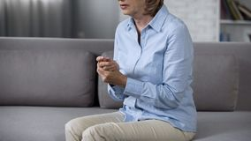 Aging woman sitting on sofa rubbing hands feeling anxious, overwhelming problems royalty free stock image