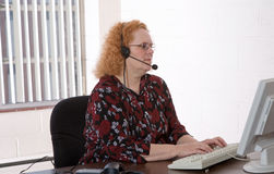 Aging Workforce. Productive middle aged woman working in a call center Stock Image