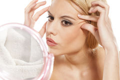 Aging wrinkles. Worried young woman checking her wrinkles around her eyes in front of a mirror royalty free stock photos