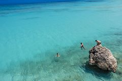Jumping into turquoise waters of Agios Ioannis Beach at Lefkada, Greece Royalty Free Stock Images