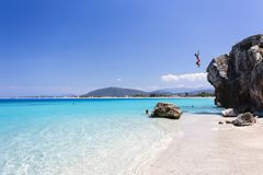 Jumping into turquoise waters of Agios Ioannis Beach at Lefkada, Greece Stock Photo