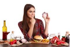 Agirl si siede ad una tavola con un pasto e tiene una metà delle cipolle in sua mano e sorride Isolato su bianco Fotografie Stock
