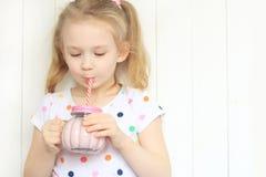 Agitação bebendo do batido da menina bonita contra o branco imagem de stock royalty free